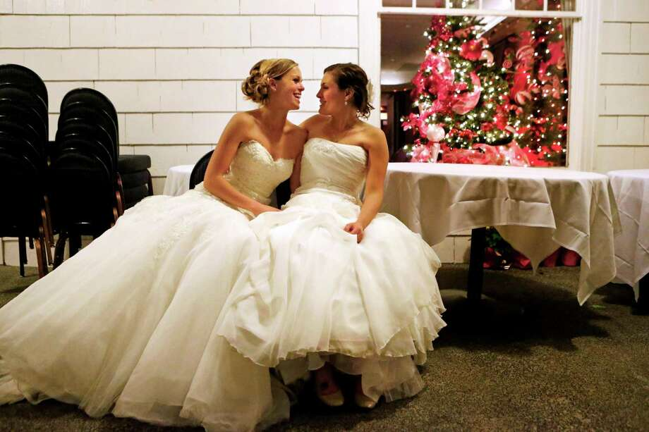 Mary Davidson, 27, left, and her bride Monica Rozgay, 29, take a breather outside in advance of their official midnight ceremony at The Seattle Yacht Club early Sunday Dec. 9, 2012.  Rozgay and Davidson, of Seattle, were one of the first couples to wed following the passage of Referendum 74, which approved a bill legalizing same-sex marriage in the state of Washington. (AP Photo/The Seattle Times, Bettina Hansen) Photo: Bettina Hansen, Associated Press / The Seattle Times