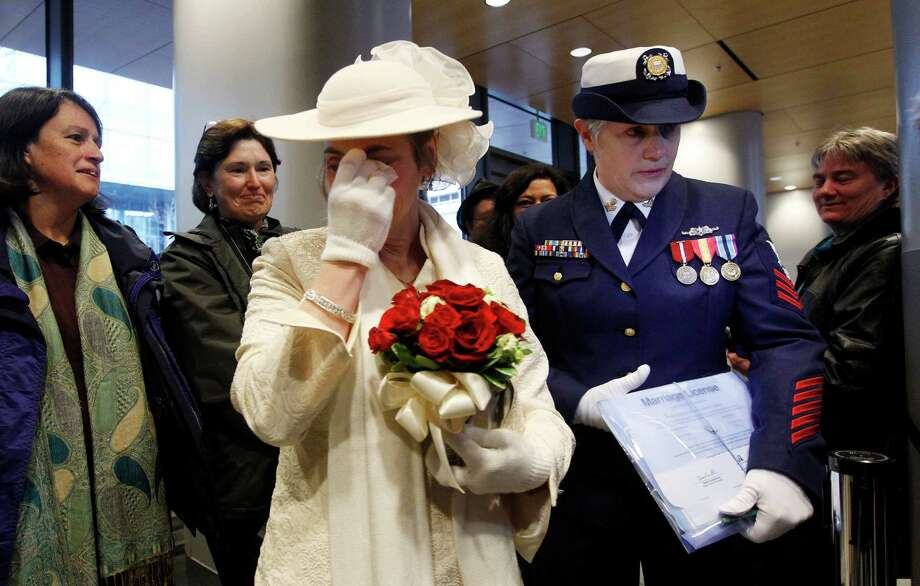 Retired U.S. Coast Guard Petty Officer 1st Class Nancy Monahan, right, wears her dress uniform and holds her marriage license as her soon-to-be bride Deb Needham wipes away tears as they wait at Seattle City Hall to become among the first gay couples to legally wed in the state Sunday, Dec. 9, 2012, in Seattle. The couple is from Renton, Wash. Gov. Chris Gregoire signed a voter-approved law legalizing gay marriage Wednesday, Dec. 5 and weddings for gay and lesbian couples began in Washington state on Sunday, following the three-day waiting period after marriage licenses were issued earlier in the week. (AP Photo/Elaine Thompson) Photo: Elaine Thompson, Associated Press / AP