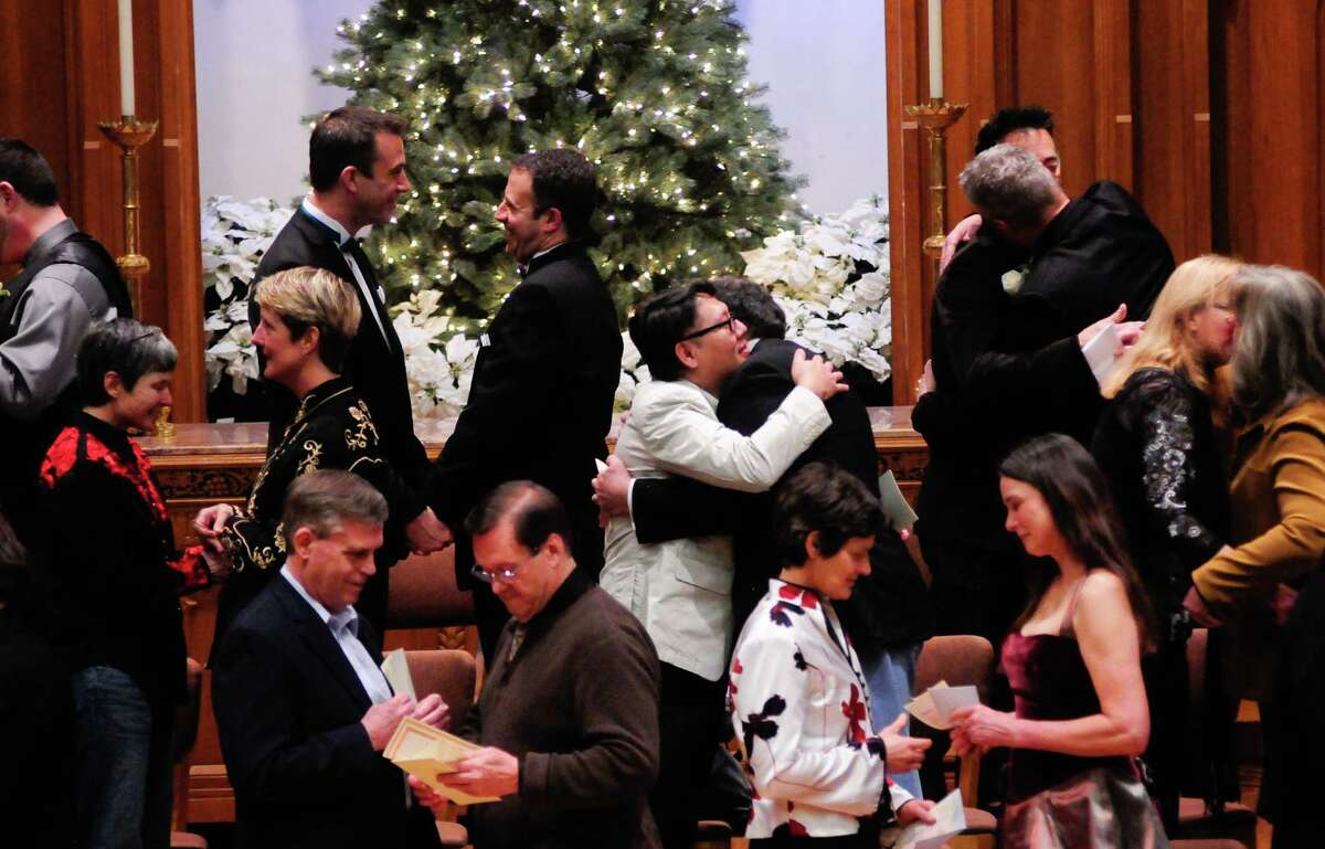 Couples hug each other and exchange vows during a Service of Marriage at the First Baptist Church on Capitol Hill in Seattle on Sunday, December 9, 2012. 25 same-sex couples were wed in a historic celebration on the first day they were legally allowed to marry.