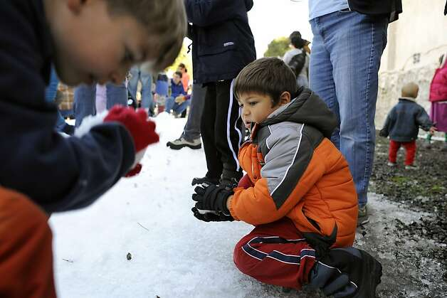 Stefan McCall(R), 5, of Berkeley packs a snowball for a battle with friends.   North Berkeley merchants are dumped 2 tons of snow into Berkeley's gourmet ghetto to give kids and families a way to frolic in the snow.  Berkeley, CA Sunday December 9th, 2012. Photo: Michael Short, Special To The Chronicle