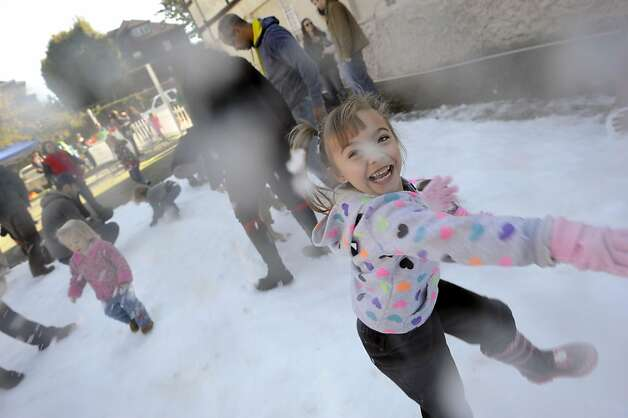 Katelyn Boone, 4, of Union City laughs as she throws a snowball.  North Berkeley merchants are dumped 2 tons of snow into Berkeley's gourmet ghetto to give kids and families a way to frolic in the snow.  Berkeley, CA Sunday December 9th, 2012. Photo: Michael Short, Special To The Chronicle