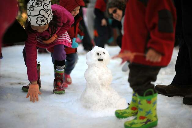 A small snowman is seen standing between children as they play in the snow.   North Berkeley merchants are dumped 2 tons of snow into Berkeley's gourmet ghetto to give kids and families a way to frolic in the snow.  Berkeley, CA Sunday December 9th, 2012. Photo: Michael Short, Special To The Chronicle