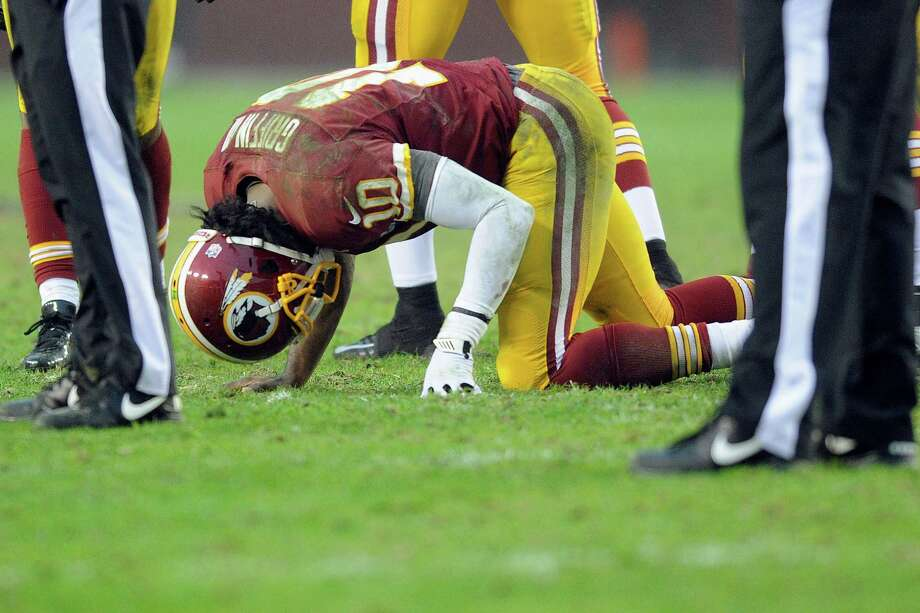 Washington quarterback Robert Griffin III is slow to get up after being tackled by Haloti Ngata at the end of a 13-yard scramble late in Sunday's game. Photo: Nick Wass, FRE / FR67404 AP