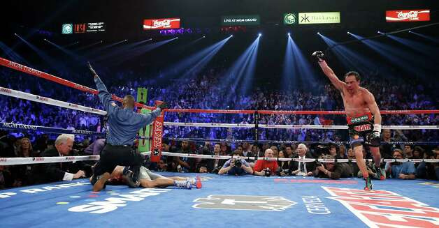 Referee Kenny Bayless, left, calls the fight as Juan Manuel Marquez, from Mexico, right, celebrates after he knocked out Manny Pacquiao, from the Philippines, lower left, in the sixth round of their WBO world welterweight  fight Saturday, Dec. 8, 2012, in Las Vegas. (AP Photo/Eric Jamison) Photo: Eric Jamison