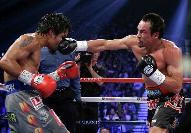 Juan Manuel Marquez, from Mexico, right, lands a right to the head of Manny Pacquiao, from the Philippines, during their WBO world welterweight  fight Saturday, Dec. 8, 2012, in Las Vegas. Marquez won by a knockout. (AP Photo/Julie Jacobson) Photo: Julie Jacobson