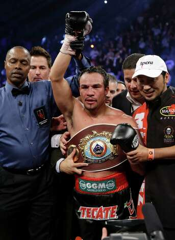 Juan Manuel Marquez, from Mexico, wears the champion's belt as his fist is raised by referee Kenny Bayless after his sixth round knockout of Manny Pacquiao, from the Philippines, in their WBO world welterweight  fight Saturday, Dec. 8, 2012, in Las Vegas. (AP Photo/Julie Jacobson) Photo: Julie Jacobson