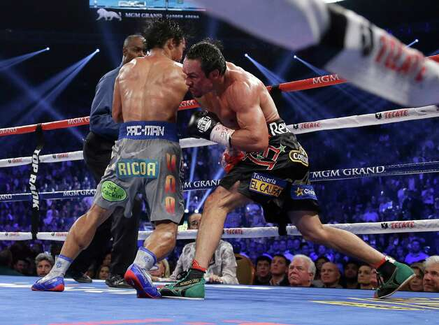 Juan Manuel Marquez, from Mexico, right, knocks out Manny Pacquiao, from the Philippines, in the sixth round of their WBO world welterweight  fight Saturday, Dec. 8, 2012, in Las Vegas. Referee Kenny Bayless looks on at left rear.  (AP Photo/Julie Jacobson) Photo: Julie Jacobson