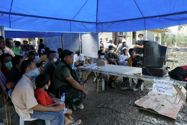 Typhoon victims as well as rescuers and soldiers take a break to watch the fight between the Philippines' Manny Pacquiao and Mexico's Juan Manuel Marquez at the command center for the rescue efforts for typhoon Bopha's victims at New Bataan township, Compostela Valley in southern Philippines Sunday Dec. 9, 2012. Filipino fans were stunned by Pacquiao's knockout defeat to Marquez on Sunday, dampening the spirit of a nation battered by a powerful typhoon that killed more than 600 people in the southern region where the boxing champion lives. (AP Photo/Bullit Marquez) Photo: Bullit Marquez