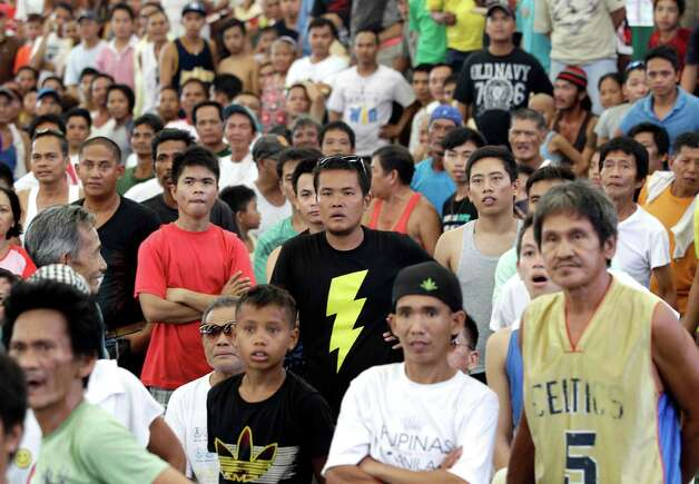 Filipinos look stunned after seeing Filipino boxing hero Manny Pacquiao was knocked out by Mexican Juan Manual Marquez during a live TV broadcast at a multi-purpose hall in suburban Paranaque, south of Manila, Philippines on Sunday, Dec. 9, 2012. Many Filipinos were stunned by Pacquiao's knockout defeat to Marquez, dampening the spirit of a nation battered recently by a powerful typhoon. (AP Photo/Aaron Favila) Photo: Aaron Favila