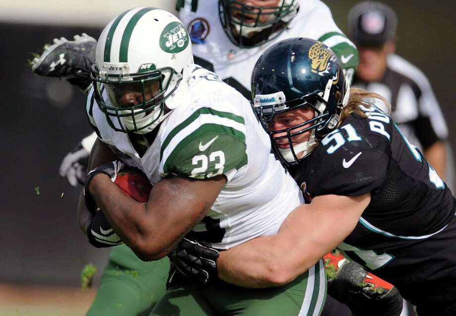 New York Jets running back Shonn Greene (23) is tackled by Jacksonville Jaguars middle linebacker Paul Posluszny (51) after a short gain during the first half of an NFL football game, Sunday, Dec. 9, 2012, in Jacksonville, Fla. (AP Photo/Stephen Morton) Photo: Stephen Morton