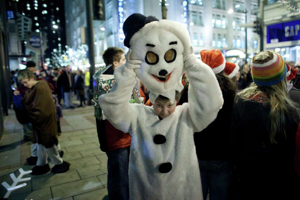 William Knox, 13, with the Glacier Peak High School and Valley View Middle School group from Snohomish puts on a Frosty the Snowman costume during The Great Figgy Pudding Street Corner Caroling Competition on Friday, December 7, 2012. The annual event brought thousands of people downtown to hear groups sing and compete to raise money for the Pike Market Senior Center & Food Bank.