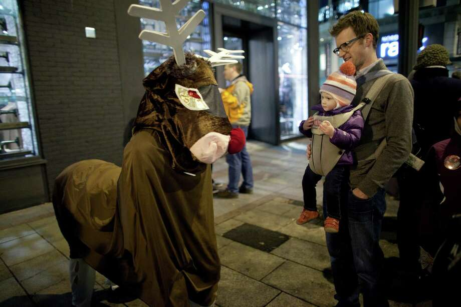 "Brian Story and Harper, 13 months, check out ""Rudolph,"" aka Cole Russon, 12, and Connor Johnson, 13, during The Great Figgy Pudding Street Corner Caroling Competition on Friday, December 7, 2012. The annual event brought thousands of people downtown to hear groups sing and compete to raise money for the Pike Market Senior Center & Food Bank. Photo: JOSHUA TRUJILLO / SEATTLEPI.COM"