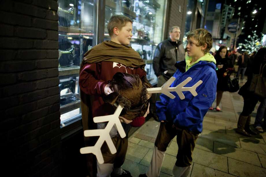 """Rudolph,"" aka Connor Johnson, 13, and Cole Russon, 12, take a break during The Great Figgy Pudding Street Corner Caroling Competition on Friday, December 7, 2012. The annual event brought thousands of people downtown to hear groups sing and compete to raise money for the Pike Market Senior Center & Food Bank. Photo: JOSHUA TRUJILLO / SEATTLEPI.COM"