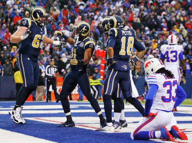 St. Louis Rams wide receiver Brandon Gibson (11) celebrates with teammates including guard Harvey Dahl (62) and wide receiver Austin Pettis (18) after catching a touchdown pass from quarterback Sam Bradford, not pictured, as Buffalo Bills cornerback Ron Brooks (33) reacts during the second half of an NFL football game, Sunday, Dec. 9, 2012, in Orchard Park, N.Y. The Rams won 15-12. (AP Photo/Bill Wippert) Photo: Bill Wippert