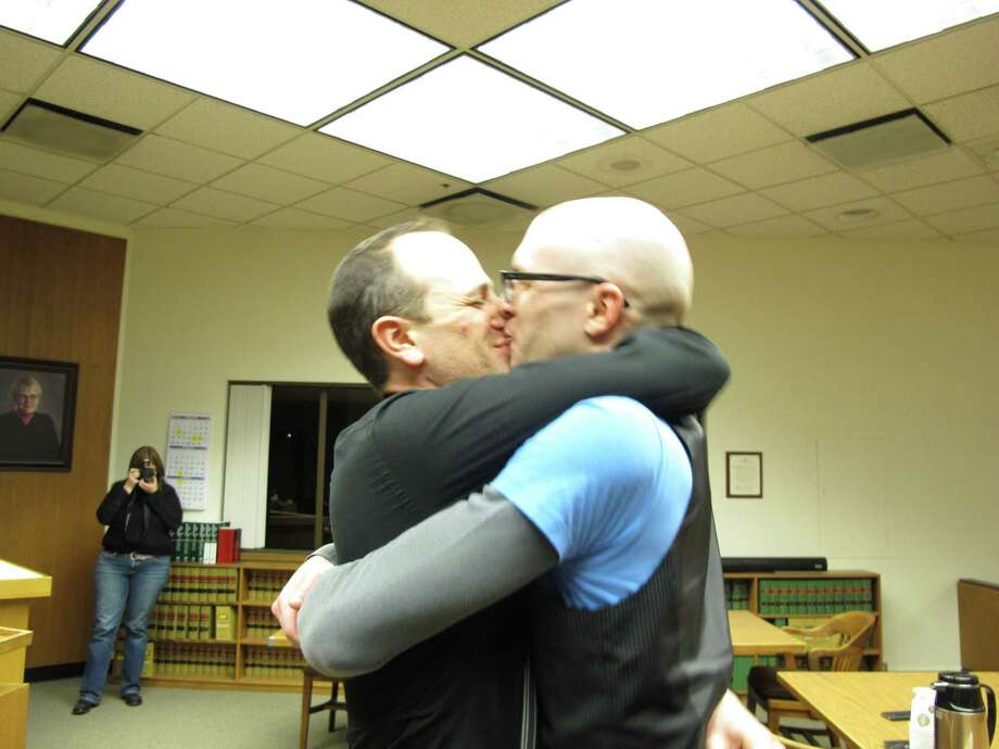 Matthew Wiltse, right, and Jonathon Bashford, left, kiss after they took their wedding vows at the Thurston County Courthouse just after midnight on Sunday, Dec. 9, 2012, in Olympia, Wash. Sunday is the first day same-sex couples can marry under Washington state's new voter-approved law allowing gay marriage. (AP Photo/Rachel La Corte) Photo: Rachel La Corte