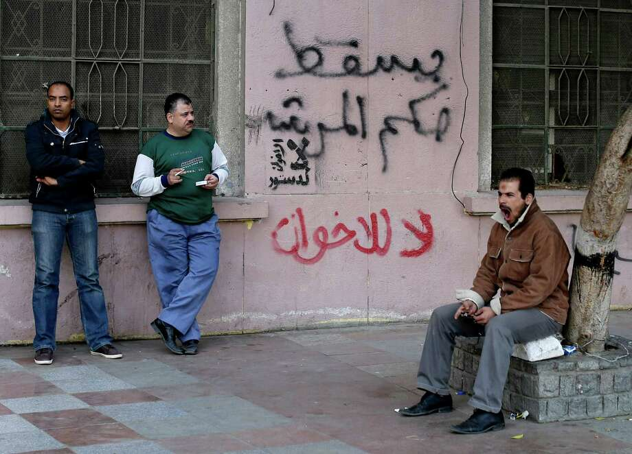 "Egyptian men stand near Arabic writing on a wall in Arabic that reads, ""down with the leader's rule, no to the Muslim Brotherhood,"" in Tahrir Square in Cairo, Egypt, Sunday, Dec. 9, 2012. Egypt's liberal opposition has called for more protests on Sunday after the president made concessions overnight that fell short of their demands to rescind a draft constitution going to a referendum on Dec. 15. (AP Photo/Hassan Ammar) Photo: Hassan Ammar"