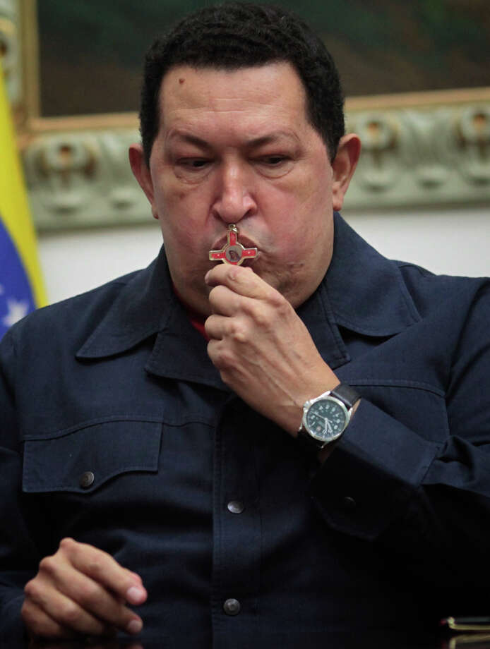 ALTERNATIVE CROP OF XFLL103,- In this photo released by Miraflores Press Office, Venezuela's President Hugo Chavez kisses a crucifix during a televised speech form his office at Miraflores Presidential palace in Caracas, Venezuela, Saturday, Dec. 8, 2012. Chavez announced Saturday night that his cancer has returned and that he will undergo another surgery in Cuba. Chavez, who won re-election on Oct. 7, also said for the first time that if his health were to worsen, his successor would be Vice President Nicolas Maduro.(AP Photo/Miraflores Press Office, Marcelo Garcia) Photo: Marcelo Garcia
