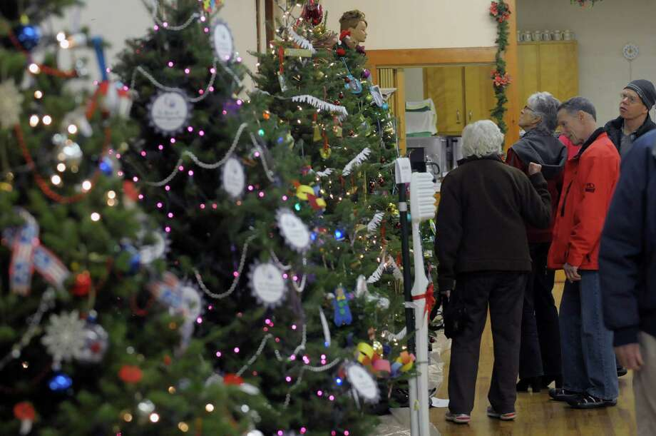 Visitors look over the Festival of Trees and Wreath Auction in the  Masonic Hall during the Victorian Holidays Celebration on Sunday, Dec. 9, 2012 in Altamont, NY.  There was also a tour of six area homes decorated for the holiday.  (Paul Buckowski / Times Union) Photo: Paul Buckowski