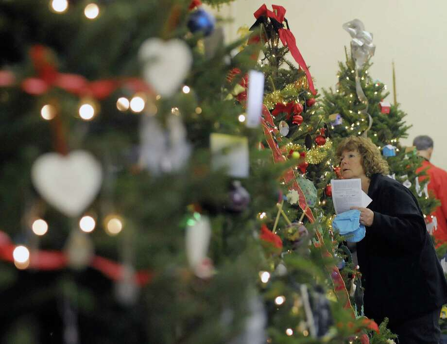 Lauri Amsden from Berne looks over a tree as she decides which one to vote for at the Festival of Trees and Wreath Auction in the  Masonic Hall during the Victorian Holidays Celebration on Sunday, Dec. 9, 2012 in Altamont, NY.  There was also a tour of six area homes decorated for the holiday.  (Paul Buckowski / Times Union) Photo: Paul Buckowski