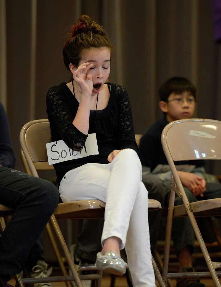 Soleil Moon representing Doyle Middle School yawns as she waits her turn to give a correct word spelling during the Seventh Annual Spelling Bee put on at W.K. Doyle Middle School by the Enlarged City School District of in Troy, N.Y. Dec. 4, 2012. (Skip Dickstein/Times Union) Photo: Skip Dickstein / 00020335A