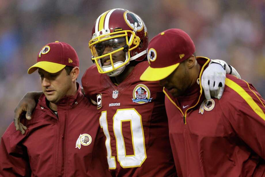 Washington Redskins quarterback Robert Griffin III is helped off the filed after an injury during the second half of an NFL football game against the Baltimore Ravens in Landover, Md., Sunday, Dec. 9, 2012. (AP Photo/Patrick Semansky) Photo: Patrick Semansky