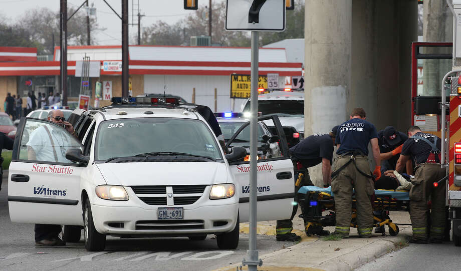 Emergency and law enforcement personnel work the scene of a shooting at the intersection of IH-10 East and Martin Luther King Boulevard, Sunday, Dec. 9, 2012. A 23-year-old man was shot in the stomach and the suspected shooter rear-ended a VIATrans van while fleeing the scene. Photo: Jerry Lara, San Antonio Express-News / © 2012 San Antonio Express-News