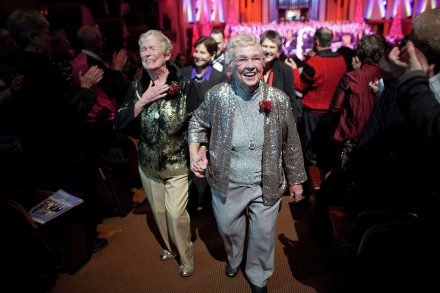 Jane Lightly, 77, and her wife Pete-e Petersen, 85, walk down the aisle after their wedding during a
