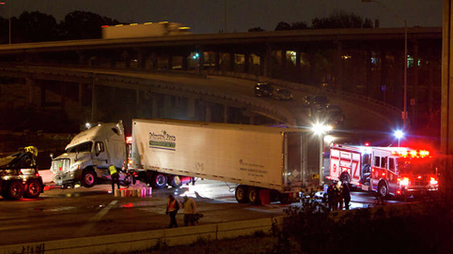 Crews prepare to tow an 18-wheeler in the West Bound lanes of I-10 East of Houston Avenue, Monday, Dec. 10, 2012, in Houston. Photo: Cody Duty, . / © 2012 Houston Chronicle