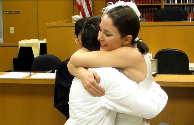 Stephanie Lyon hugs her bride, Margaret Ryan, after they were married on the first day that same-sex unions were legal in Washington State. The couple met in 2005 when Ryan rescued Lyon from her burning apartment building. Photo: Casey McNerthney/seattlepi.com
