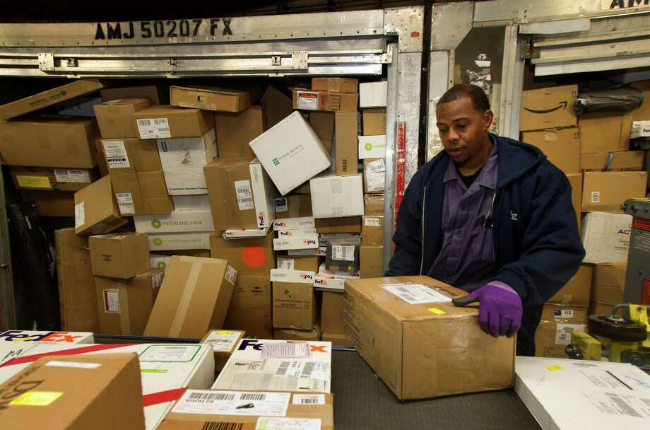 Prettice Fanniel puts a box on the conveyor belt at the FedEx wharehouse Monday, Dec. 10, 2012, in Houston. Monday is the busiest day of the year in the company's history. They will ship 19 million packages globally today. Photo: Cody Duty, Houston Chronicle / © 2012 Houston Chronicle