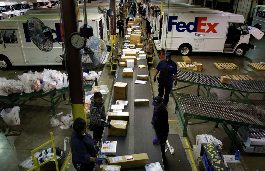 Employees sort out boxes before they're put on a truck for delivery at the FedEx warehouse Monday, Dec. 10, 2012, in Houston. Monday is the busiest day of the year in the company's history. They will ship 19 million packages globally today. Photo: Cody Duty, Houston Chronicle / © 2012 Houston Chronicle