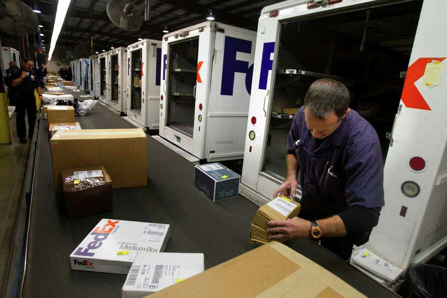 Kenneth Easterly sorts out boxes before they're put on a truck for delivery at the FedEx warehouse M