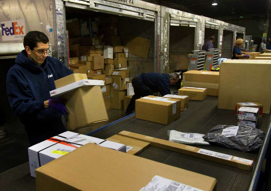 Aaron Azios sorts out boxes from cargo carriers that came from the airport at the FedEx warehouse Monday, Dec. 10, 2012, in Houston. Monday is the busiest day of the year in the company's history. They will ship 19 million packages globally today. Photo: Cody Duty, Houston Chronicle / © 2012 Houston Chronicle