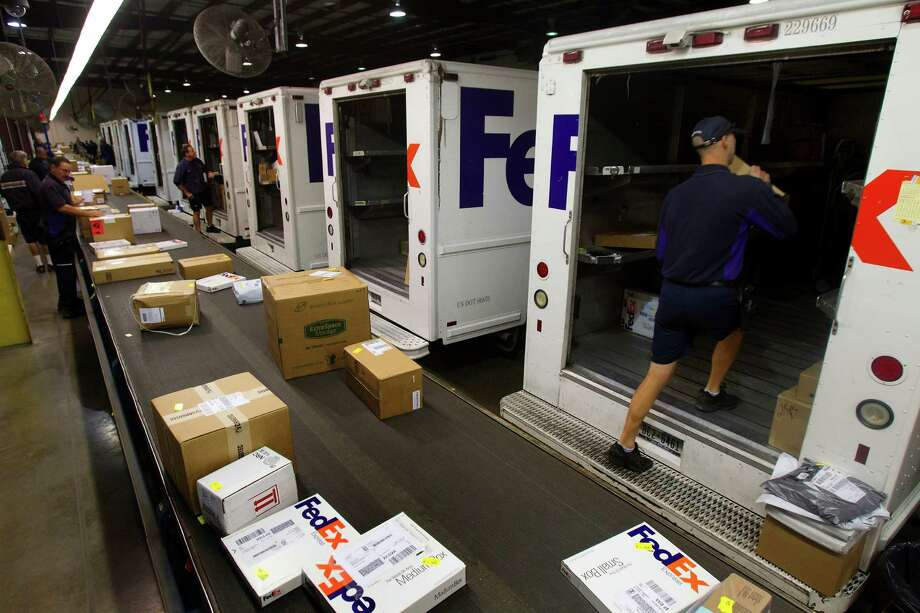 Hunter Triplett, right, loads a package onto a delivery truck at the FedEx warehouse Monday, Dec. 10, 2012, in Houston. Monday is the busiest day of the year in the company's history. They will ship 19 million packages globally today. Photo: Cody Duty, Houston Chronicle / © 2012 Houston Chronicle