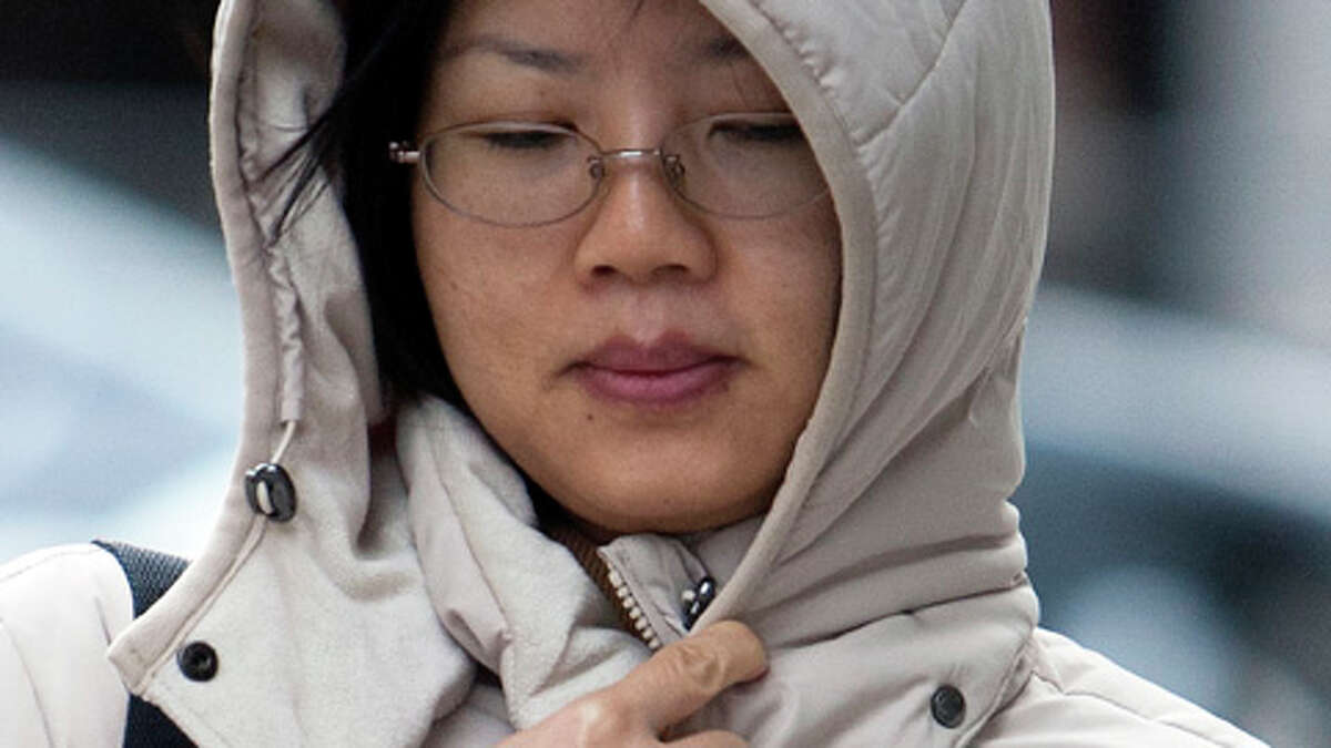 Bethany Kwok bundles up as she walks along Walker Street, Monday, Dec. 10, 2012, in Houston. Kwok said that is was the more the wind that was making the weather really cold.