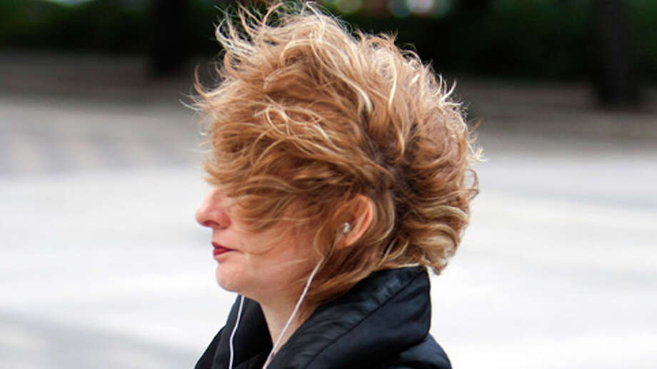 "Gracie Orr's hair blows in her face as she walks along Walker Street, Monday, Dec. 10, 2012, in Houston. ""It's even worse down here because of the buildings,"" she said of the wind. Photo: Cody Duty, . / © 2012 Houston Chronicle"