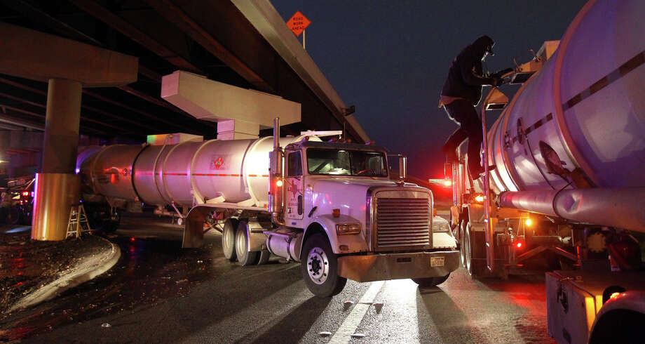 "Crude oil is unloaded from one tanker truck to another after one of the trucks (left) hit a bridge pillar shortly before 3:00 a.m. Monday December 10, 2012 under Interstate Highway 35 near Loop 410 North and Randolph Boulevard. San Antonio Fire Department Assistant Chief Oscar Gonzalez about half of the 8,500 gallon load of crude in the truck leaked out but was contained and remediated by the Texas Department of Transportation. Gonzalez said Randolph Boulevard was blocked under IH-35 and there were no injuries during the incident. A sign on the door of the truck read ""Alpha Petroleum Transport"" from Houston. Photo: John Davenport/Express-News"