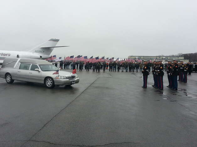 Members of the U.S. Marines, the Patriot Guard and the family of Lance Cpl. Anthony Denier wait for his body to arrive at Albany International Airport on Monday, Dec. 10, 2012. (DENNIS YUSKO / TIMES UNION)