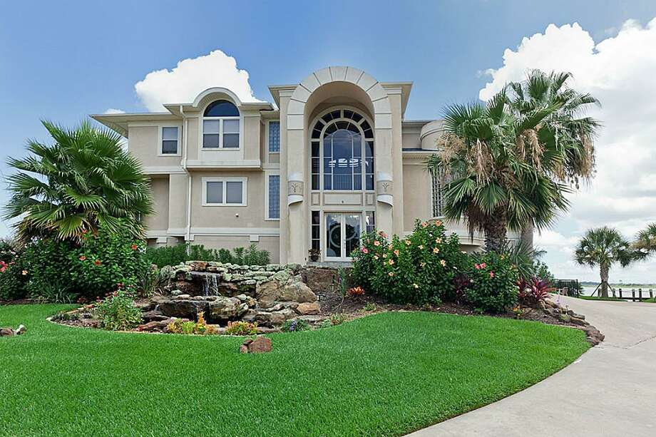 The frontage of 158 Sandy Cove contains a well-manicured lawn, waterfall and several mature palms. Photo: Better Homes And Gardens
