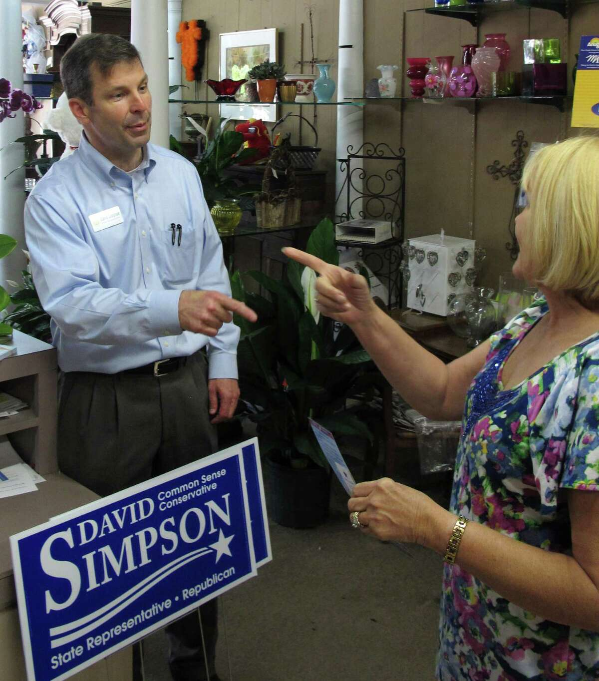 Republican state Rep. David Simpson, left, chats with flower shop employee Jaime Taylor, right, while campaigning April 25, 2012, in Longview, Texas. Simpson is a strident conservative and tea party favorite who faces the man he beat two years ago, former state Rep. Tommy Merritt, in the Texas Republican primary May 29. (AP Photo/Will Weissert)