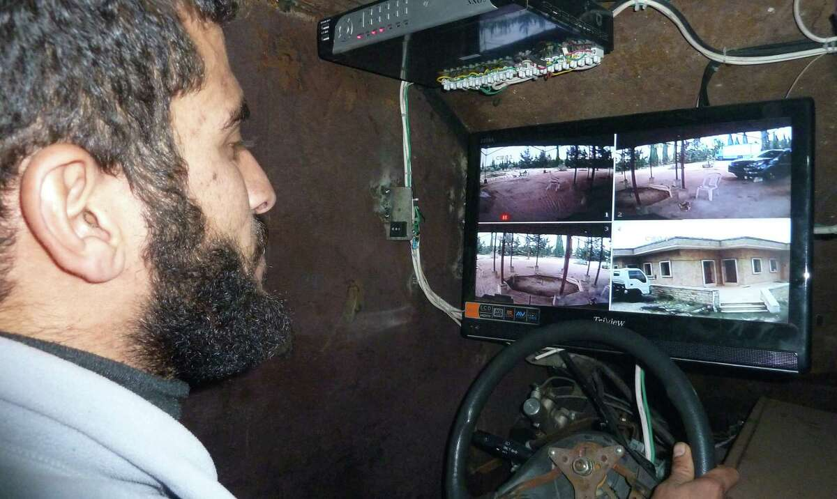 A Syrian rebel drives Sham II, navigating via displays connected to five cameras --  three at the front, one in the back and one attached to the gun -- in Bishqatin, west of Aleppo, Syria on Dec. 8, 2012.