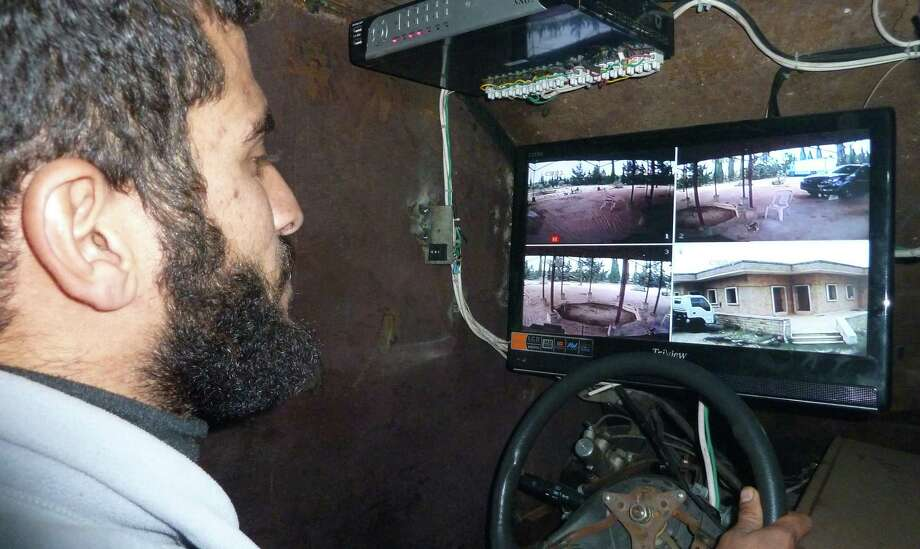 A Syrian rebel drives Sham II, navigating via displays connected to five cameras --  three at the front, one in the back and one attached to the gun --  in Bishqatin, west of Aleppo, Syria on Dec. 8, 2012. Photo: AFP, AFP/Getty Images / 2012 AFP