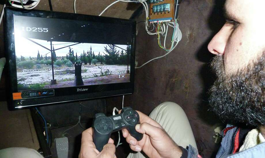 A Syrian rebel uses what appears to be a PlayStation controller to activate the 7.62-mm machine gun of Sham II, in Bishqatin, west of Aleppo, Syria on Dec. 8, 2012. Photo: AFP, AFP/Getty Images / 2012 AFP