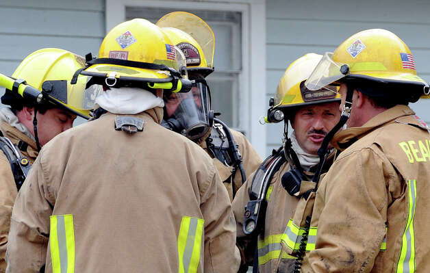 Beaumont firefighters after extinguishing a house fire on the 3700 block of Lynwood Monday morning. Beaumont Police say the fire is thought to have been started by a 12-year-old boy. A neighbor said the boy was home alone when the fire occurred. No injuries were reported. Photo taken December 10, 2012 Guiseppe Barranco/The Enterprise Photo: Guiseppe Barranco, STAFF PHOTOGRAPHER / The Beaumont Enterprise