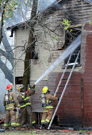 Firefighters shoot water into a smoking home on Avenue I Monday morning. Beaumont Firefighters say the blaze began while a resident was using a propane heater to warm his home. The fire also destroyed the home next door. No injuries were reported from the fire.  Photo taken December 10, 2012 Guiseppe Barranco/The Enterprise Photo: Guiseppe Barranco, STAFF PHOTOGRAPHER / The Beaumont Enterprise