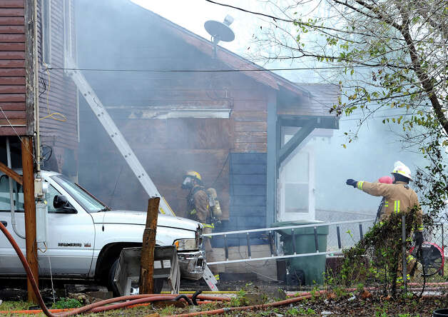 Firefighters work to extinguish a smoking home on Avenue I Monday morning. Beaumont Firefighters say the blaze began while a resident was using a propane heater to warm his home. The fire also destroyed the home next door. No injuries were reported from the fire.  Photo taken December 10, 2012 Guiseppe Barranco/The Enterprise Photo: Guiseppe Barranco, STAFF PHOTOGRAPHER / The Beaumont Enterprise