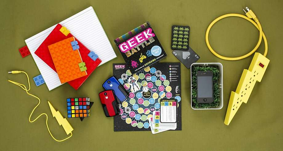 To enhance cubicle life, stash building block notebooks ($18 and $20, www.pylones-usa.com) for taking notes by hand, on paper after a power failure or random act of a vengeful life form. Pencil, pen or quill not included. To combat boredom, break out Geek Battle ($19.95, www.chroniclebooks.com) or Space Invader playing cards ($10, www.kikkerland). While the grassy charging station ($32, www.kikkerland.com) and the lightening bolt power strip ($20, www.fredflare.com)with its sparky cousin, a 4-port USB hub ($15, www.kikkerland.com) add a certain je ne sais quoi to workspace décor, they lack the functionality of the two PowerBar 4200s ($69.95, www.fatcatgear.com)which can charge your smartphone in an emergency.  When you're stuck on musical hold, time yourself on the Rubik's Cube 5 x 5 ($32.95, www.exploratorium.edu). You may finish before being offered excellent customer service. Photo: Russell Yip, The Chronicle