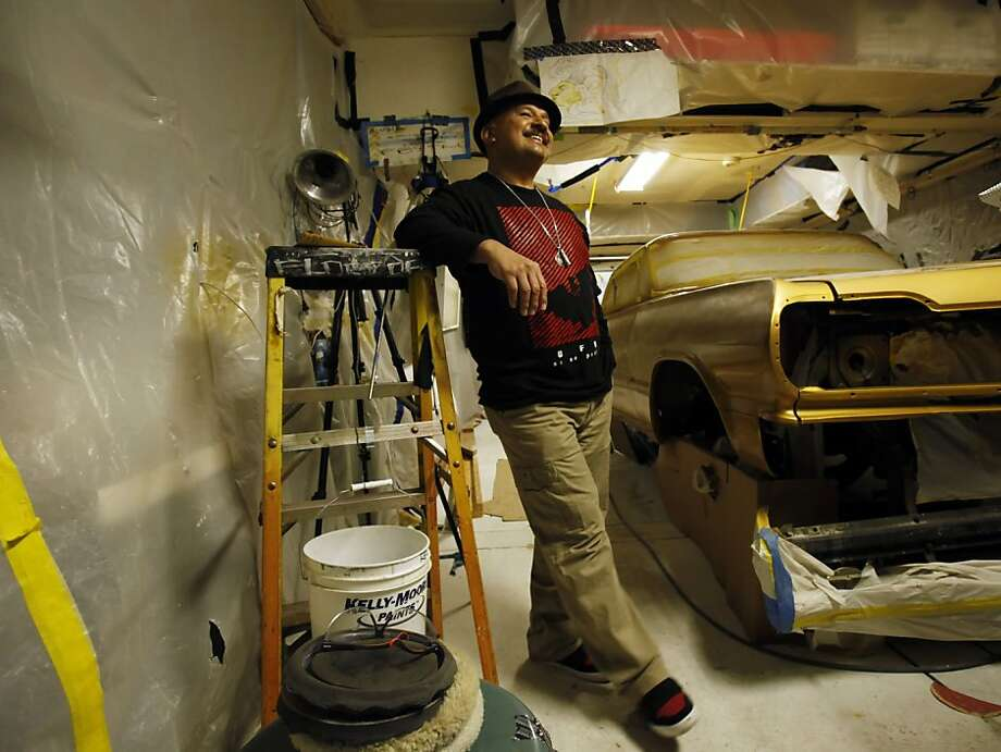 Roberto Hernandez stands next to Chevy Impala that he is restoring as a low rider in a garage in San Francisco, Calif., on Tuesday, November 27, 2012. Hernandez is an artist and has taken to training neighborhood kids how to paint low riders to keep them out of trouble in the Mission district of San Francisco, Calif. Photo: Carlos Avila Gonzalez, The Chronicle