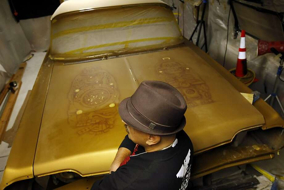 Roberto Hernandez stands next to a Chevy Impala that he is restoring as a low rider in a garage in San Francisco, Calif., on Tuesday, November 27, 2012. Hernandez is an artist and has taken to training neighborhood kids how to paint low riders to keep them out of trouble in the Mission district of San Francisco, Calif. Photo: Carlos Avila Gonzalez, The Chronicle