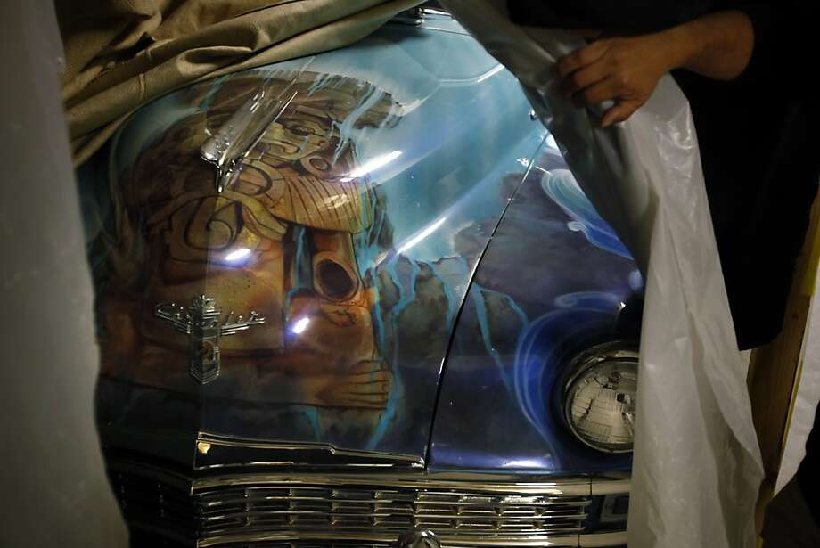 Roberto Hernandez pulls back the cover to reveal the Mayan-themed art on his vintage Chrysler. Photo: Carlos Avila Gonzalez, The Chronicle